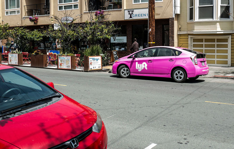 A Lyft-branded car picks up a passenger in San Francisco on June 20, 2015.