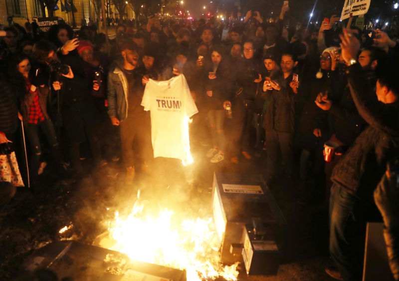 Protesters set a Trump T-shirt on fire in the street as they make themselves heard following the inauguration of President Donald Trump on January 20, 2017 in Washington, DC.