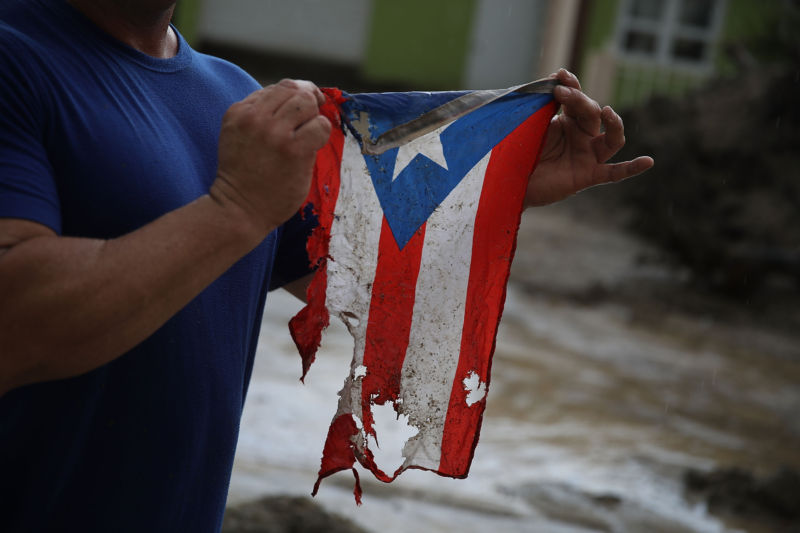 UTUADO, PUERTO RICO - OCTOBER 06:  Jose Javier Santana holds a Puerto Rican flag he found on the ground after Hurricane Maria passed through.
