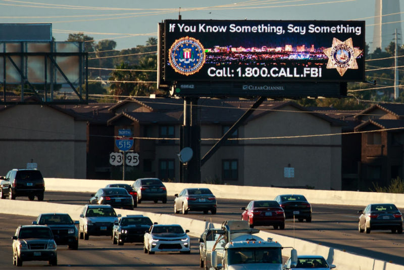 Vehicles drive past a Las Vegas billboard featuring a Federal Bureau of Investigation tip line number on Interstate 515. On October 1, Stephen Paddock killed 58 people and injured more than 450 after he opened fire on a large crowd at the Route 91 Harvest country music festival.