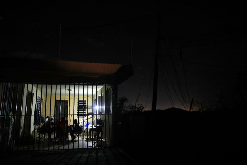 SAN ISIDRO, PUERTO RICO - OCTOBER 07:  People sit in their home lit by a single donated solar lamp more than two weeks after Hurricane Maria hit the island. (Photo by Mario Tama/Getty Images)