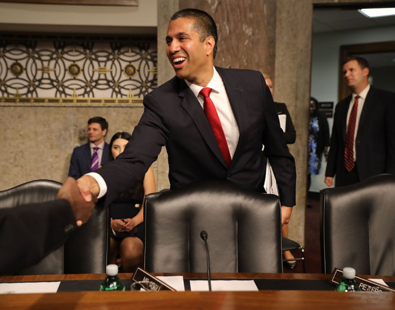 FCC Chairman Ajit Pai smiling and shaking someone's hand at his Senate confirmation hearing.