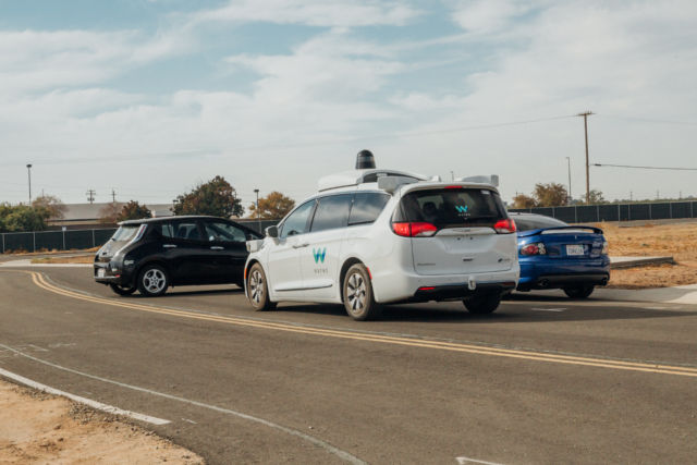 A Waymo vehicle during testing. In this scenario, a car unexpectedly backed out in front of the Waymo self-driving van. The Waymo vehicle was able to stop even though the reversing car was initially mostly obscured by another car in front of it.