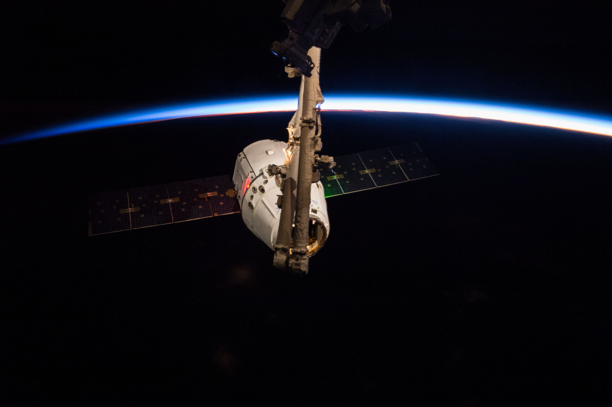A robotic arm grabs SpaceX's Dragon spacecraft in 2015.