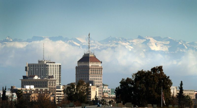 Downtown Fresno's skyline can be seen below snow caps the Sierra Nevada mountains and clouds along the foothills.