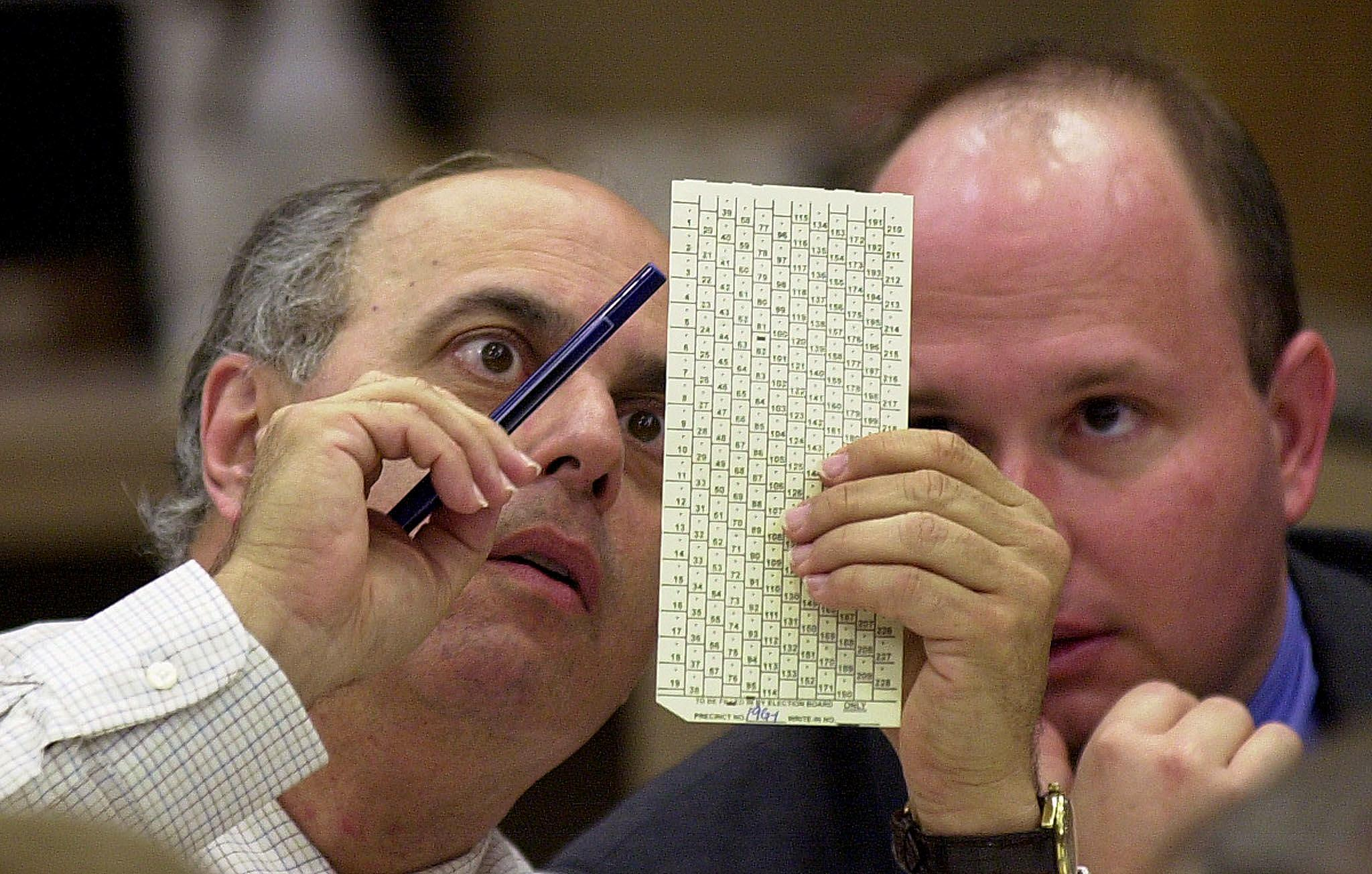 Broward County Canvassing Board Member Judge Robert Rosenberg (L) shows a ballot to an unidentified observer at the Broward County Courthouse in Ft. Lauderdale, Florida in November 2000. This is why we can't have nice things.