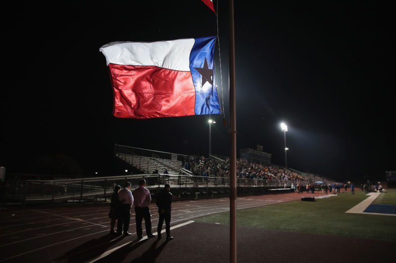A Texas flag flies at half mast during prayer services at the La Vernia High School Football stadium to grieve the victims killed at the First Baptist Church of Sutherland Springs.