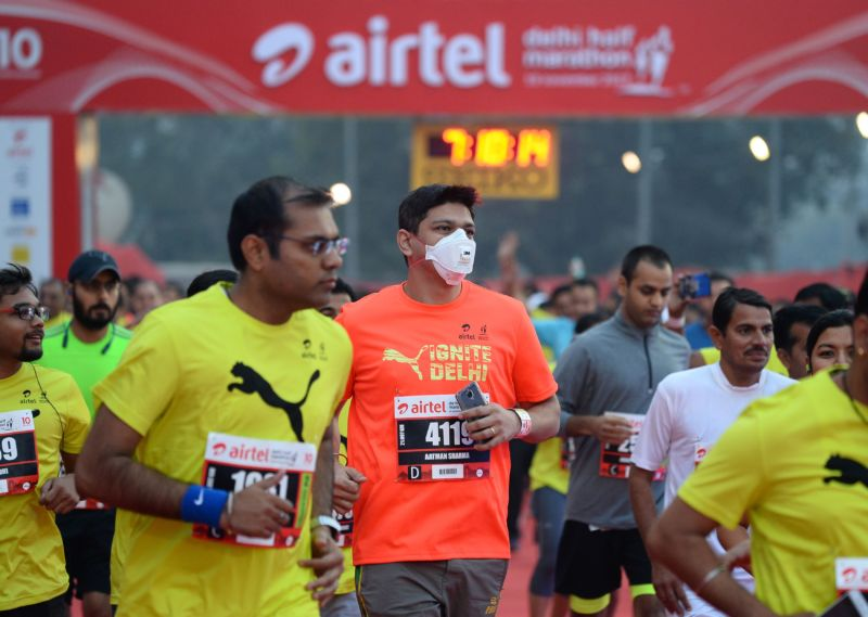 A man wears a face mask as he takes part in the Airtel Delhi Half Marathon 2017 in New Delhi on November 19, 2017.