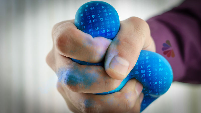 A Comcast employee's hand squeezing a stress ball imprinted with Internet data.