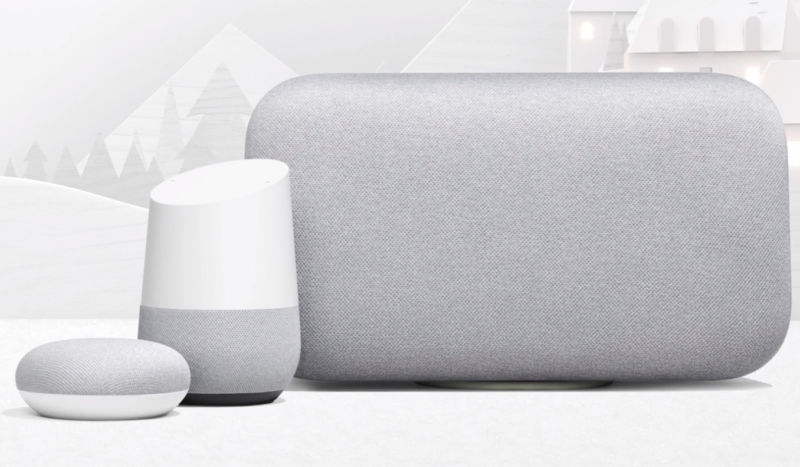 Three different Google Home smart speakers sit one next to each other on a table.