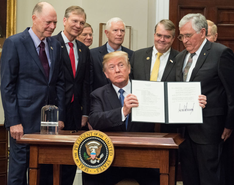 President Donald Trump holds up the Presidential Space Directive-1 after signing it.