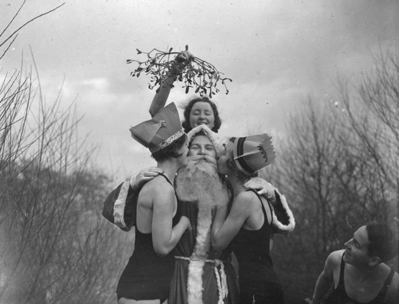 26th December 1936:  Father Christmas getting a kiss under the mistletoe.