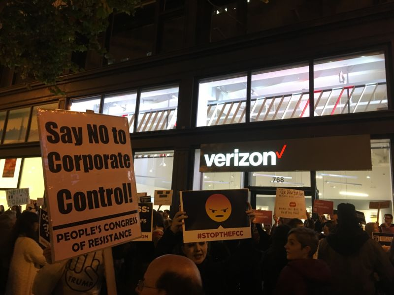 "Protestors waved signs saying ""Say no to corporate control"" and ""StopTheFCC."""