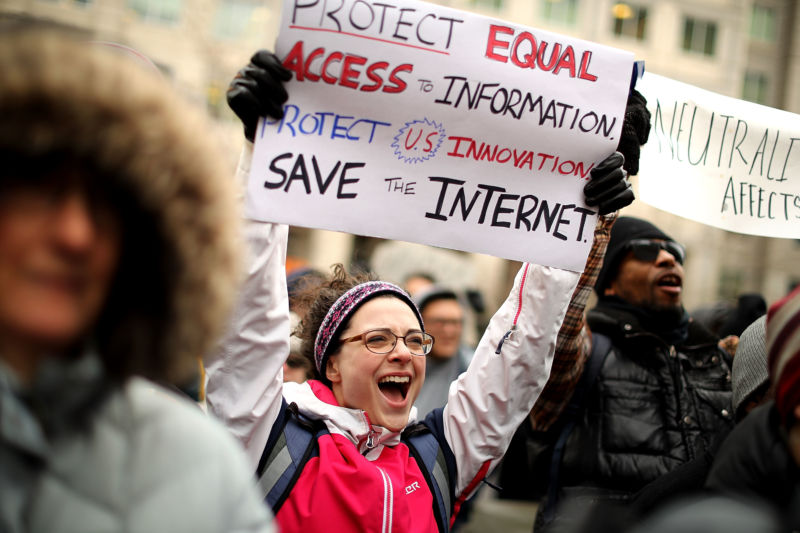 Net neutrality supporters holding signs protesting the FCC's repeal of net neutrality rules.