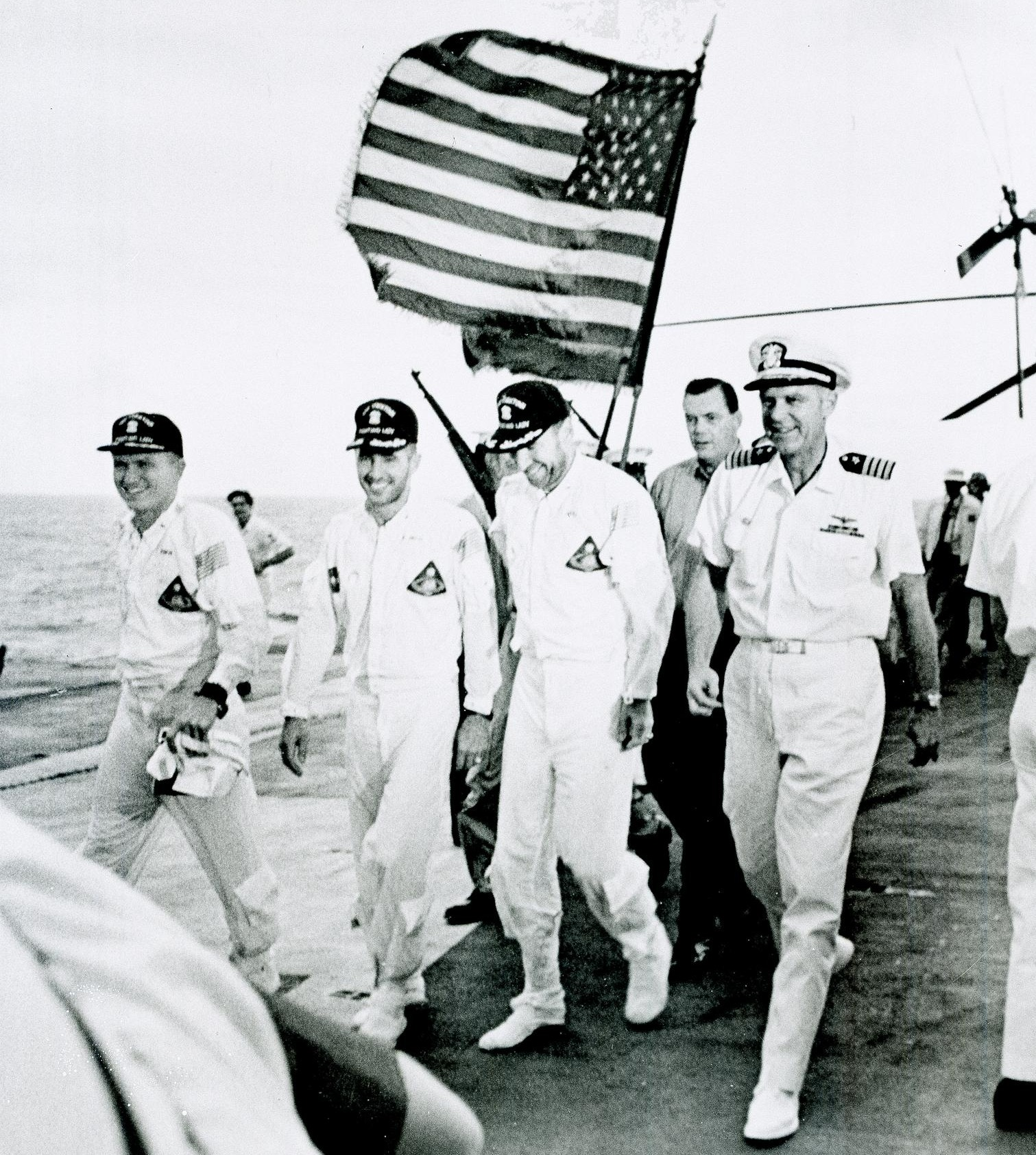 Apollo 8 astronauts and commanding officer of the recovery ship USS <em>Yorktown</em> walk the red carpet of the flight deck after splashdown recovery in the Pacific Ocean.