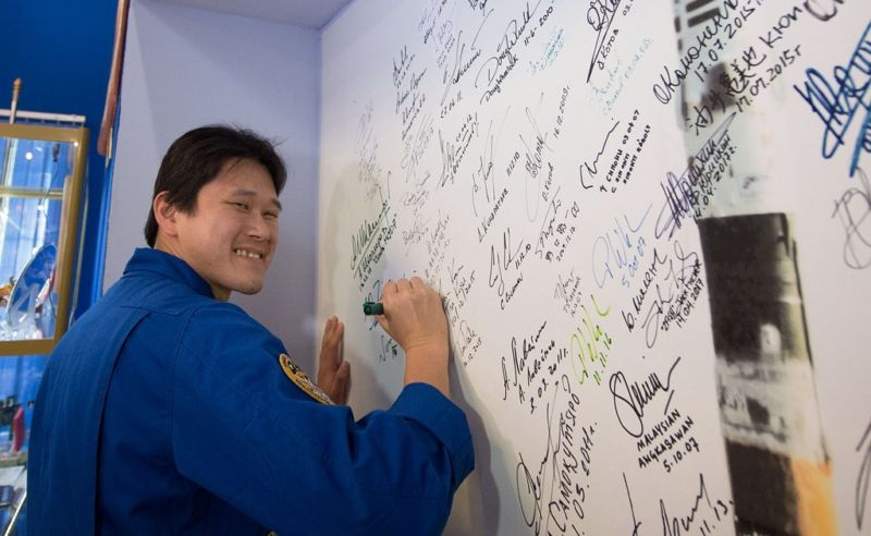 At the Korolev Museum at the Baikonur Cosmodrome in Kazakhstan, Norishige Kanai signs a wall mural Dec. 13 as part of traditional pre-launch ceremonies.