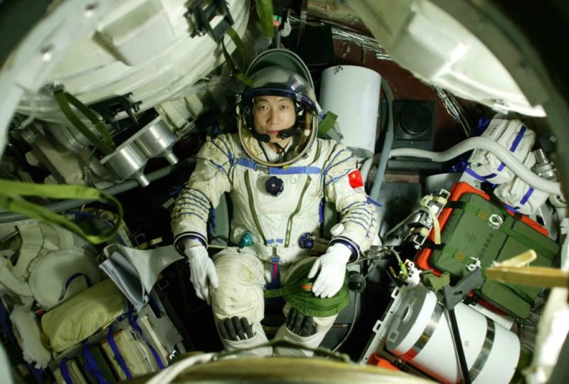 Astronaut Yang Liwei lies in the re-entry capsule of Shenzhou-5 Spacecraft during a training on September 27, 2003 in Beijing, China.