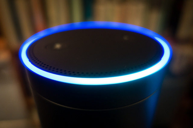 Amazon's Echo smart speaker with its blue light ring illuminated.
