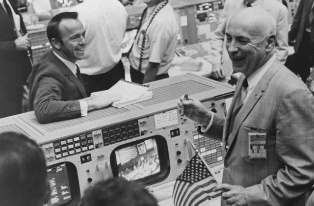 Cigars and US flags dot the Mission Control Center in Houston on May 26 after successful completion of the Apollo 10 Moon mission. Among the celebrants are Alan Shepard (left), who was the first US man in space, and Robert Gilruth (right), Director of the Space Center.
