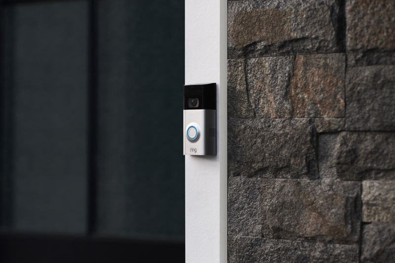 Smart doorbell between a door and a brick wall.