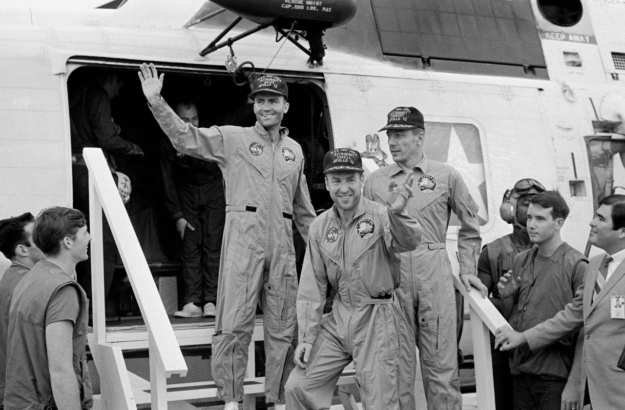 Fred Haise, left, Jim Lovell, center, and Jack Swigert step onto the deck of the <em>Iwo Jima</em> aircraft carrier.