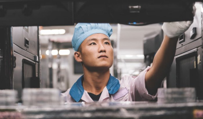 An iPhone assembly worker works with Apple supplier Pegatron in an image distributed by Apple.