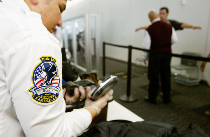 A Transportation Security Administration baggage screener inspects an electronics device as a man is screened in the background at the international terminal of San Francisco International Airport August 5, 2003 in San Francisco, California.