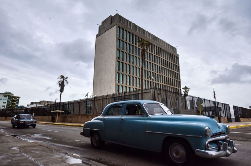 1950s cars driving past a Brutalist, multistory concrete building is peak Cuba.