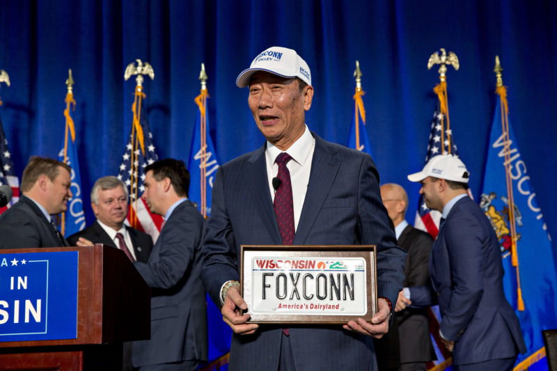 "Billionaire Terry Gou, chairman of Foxconn Technology Group, holds a ""FOXCONN"" Wisconsin license plate during an event in Racine, Wisconsin, on Friday, November 10, 2017. The agreement grants the electronics giant $3 billion in tax incentives for a massive manufacturing campus in Southeastern Wisconsin."