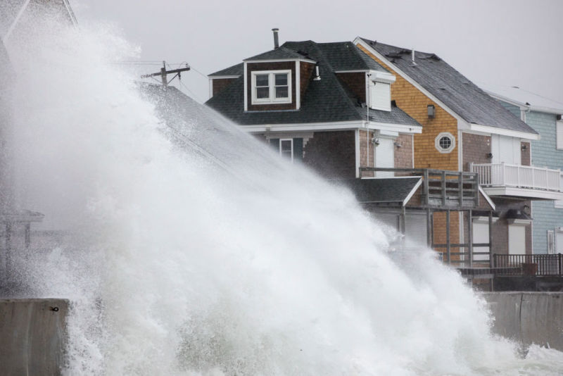 Waves crash over houses on Turner Rd. as a large coastal storm affects the area on March 2, in Scituate, Massachusetts. A powerful nor'easter is bringing snow, rain, and high wind to much of the Northeast.