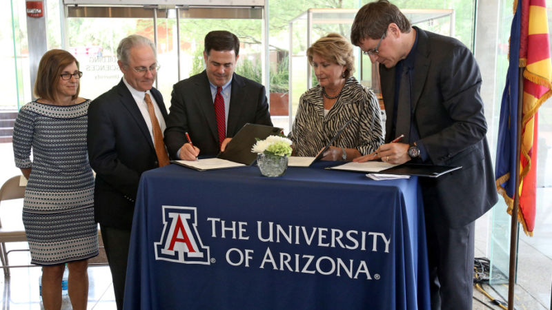 Gov. Doug Ducey, third left, signs an agreement on August 25, 2015 with University of Arizona President Ann Weaver, second right, and Brian McClendon, the vice president for Uber, which will allow them to test and do research on driverless technology in the Tucson area.