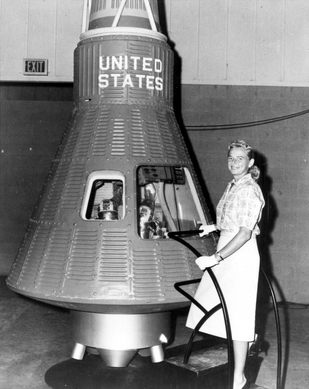 "Jerrie Cobb, one of the ""Mercury 13,"" poses next to a Mercury spaceship capsule."