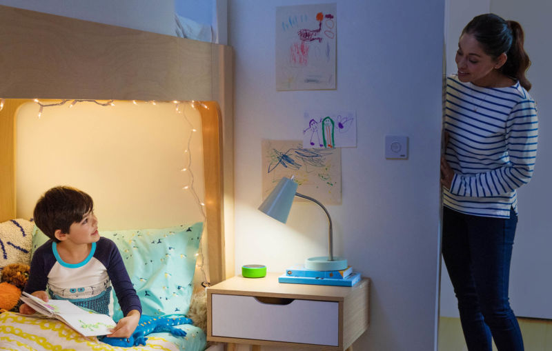 A child in bed reading next to a nightstand with an Amazon Echo Dot Kids Edition on it.