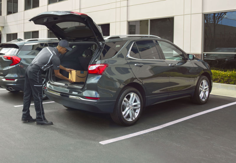 Amazon courier delivering a package inside the trunk of a Chevrolet car.