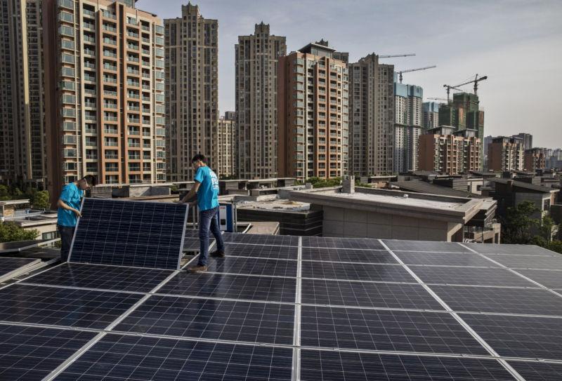 WUHAN, CHINA - APRIL 27: Workers from Wuhan Guangsheng Photovoltaic Company install solar panels on the roof of a building on April 27, 2017 in Wuhan, China.  (Photo by Kevin Frayer/Getty Images)