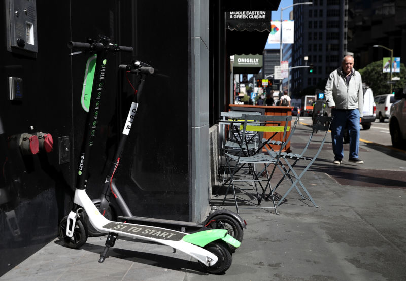 Bird and Lime scooters sit parked in front of a building on April 17, 2018 in San Francisco.