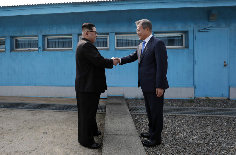 North Korean Leader Kim Jong Un (L) and South Korean President Moon Jae-in (R) shake hands over the military demarcation line