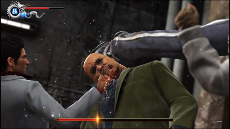 Kazuma punches a man in the skull as an associate kicks him from the other side.