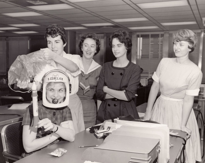 Black-and-white photo of young women joking around in an office.