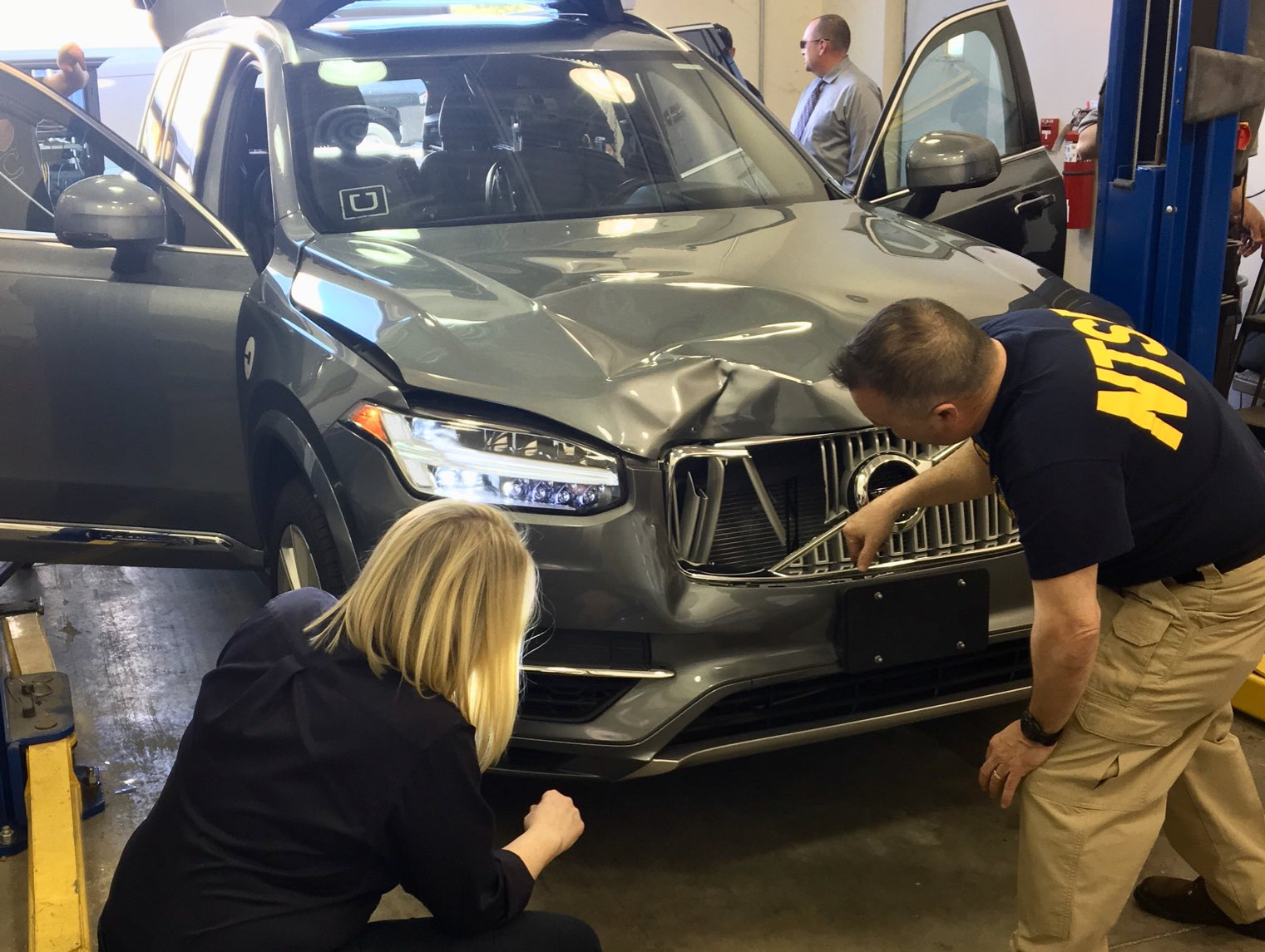 NTSB investigators inspect the self-driving Uber car that killed pedestrian Elaine Herzberg in March.