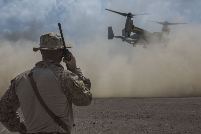A US Marine in fatigues watches a helicopter land in a desert.