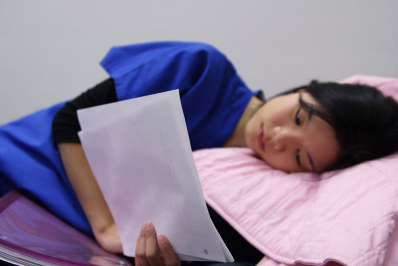 Image shows a person reading papers while lying down.