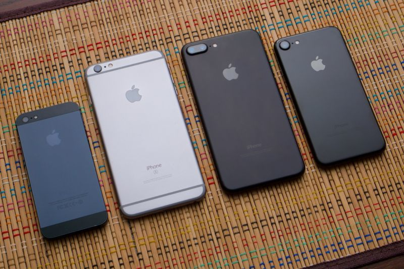 Various iPhone models laying face-down on a multicolored table mat.