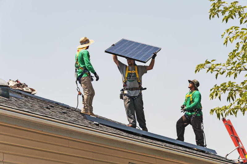 Men on roof, one holding solar panel.