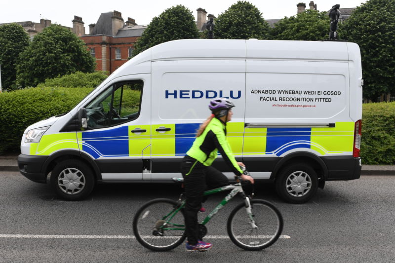 A marked police van drives past a bicyclist in the Welsh countryside.