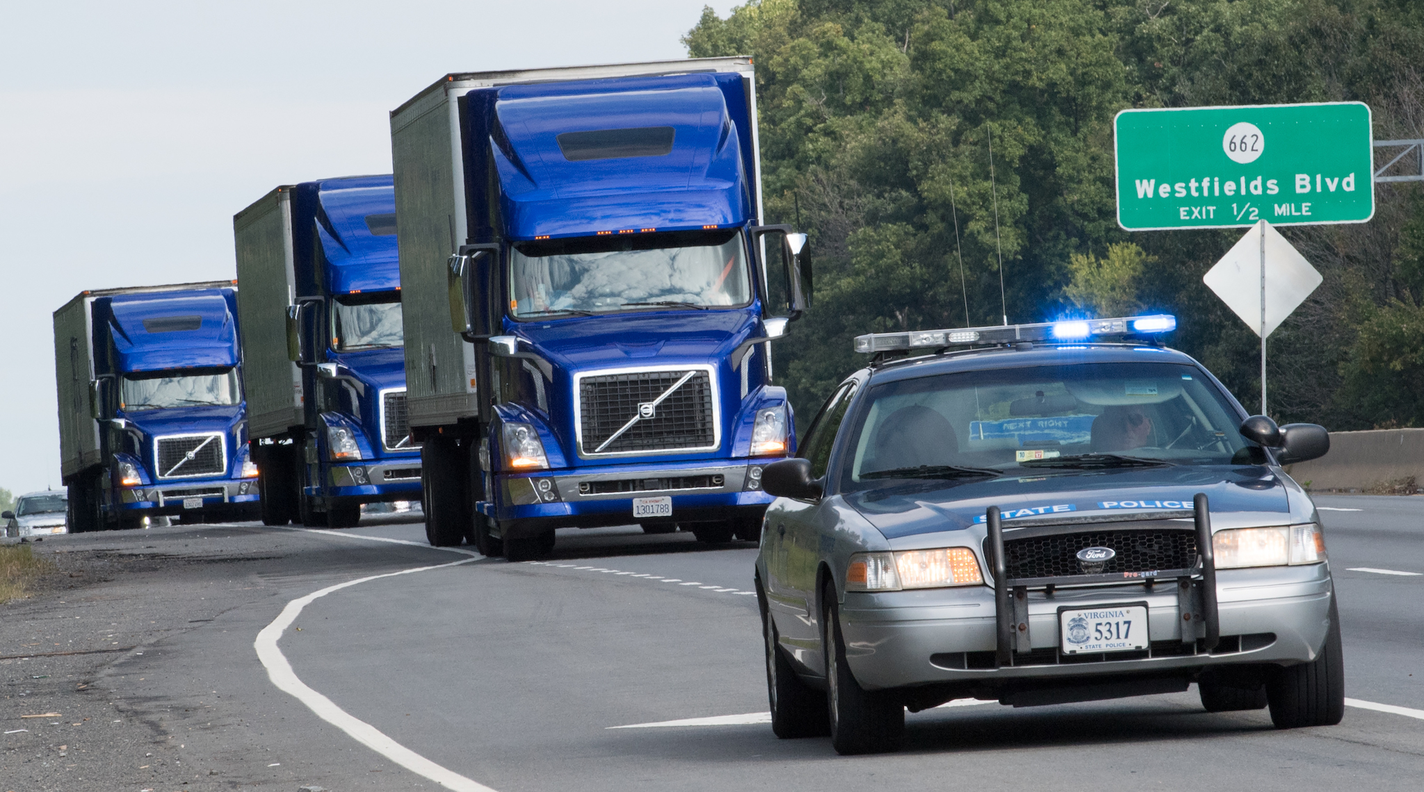 The US Federal Highway Administration conducts demonstrations of partially automated semi-truck platoons September 14, 2017, as three specially equipped Volvo semi-trucks cruise in Centreville, Virginia, with a Virginia State Trooper escort.