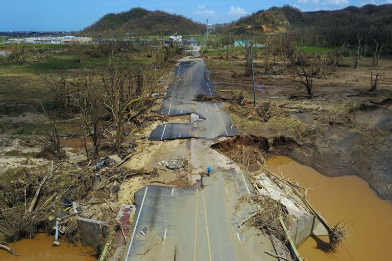 A torn-up road cuts through devastated countryside.