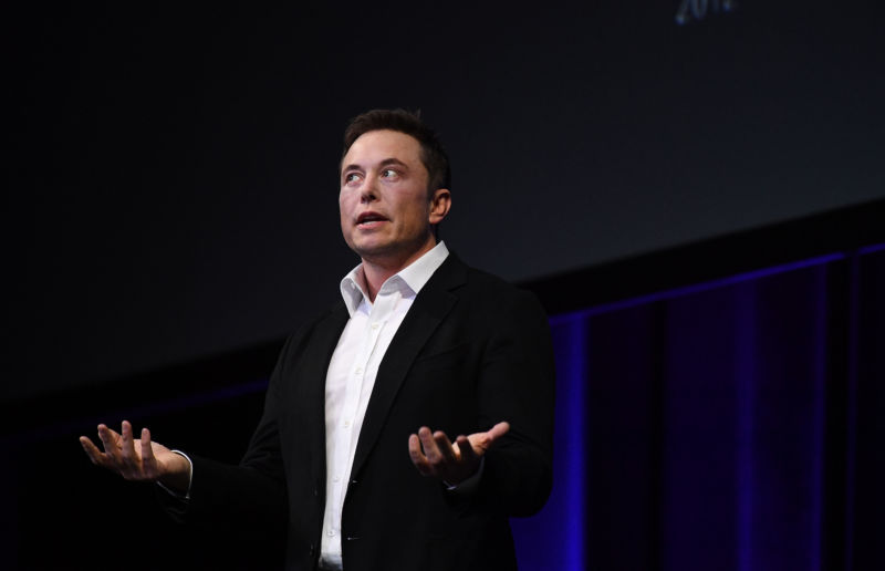 Elon Musk gives a talk on a stage.