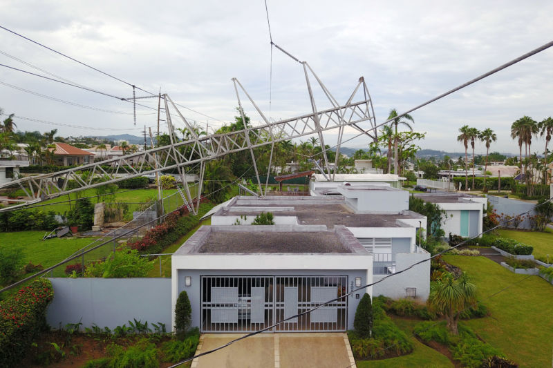 "A power line tower downed by the passing of Hurricane Maria lies on top of a house in San Juan, Puerto Rico, on November 7, 2017.  The Center for Puerto Rican Studies at Hunter College in New York estimated in a report released last month that about 114,000 to 213,000 Puerto Rican residents will leave the island annually ""as a result of Hurricane Maria."""