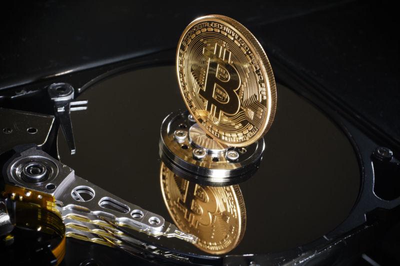 Image of a bitcoin balanced on a hard drive.